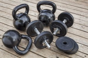 16529556-exercise-weights--kettlebells-and-dumbbells-on-a-wooden-deck--a-home-gym-concept